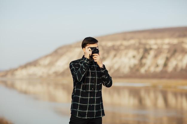 旅行中に山でビンテージカメラで写真を撮る若いスタイリッシュな男の写真家。
