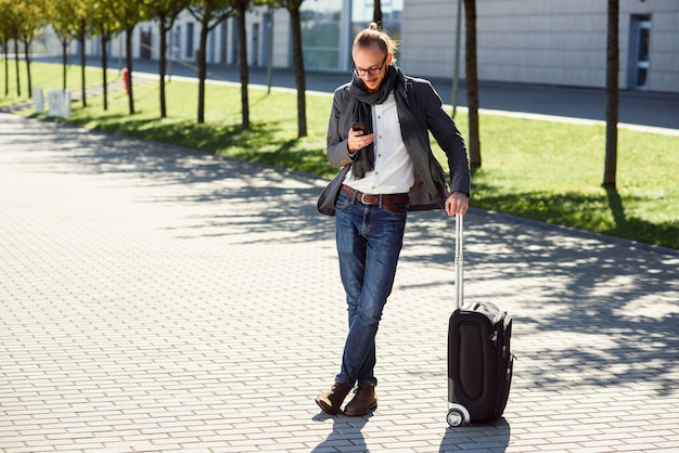 Young stylish man using his smartphone while standing with suitcase near exit the airport outdoors. business style, traveler, modern lifestyle, business trip.