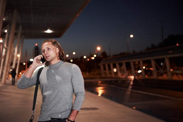 Young stylish man walking through the night street near the road and having a conversation on the phone