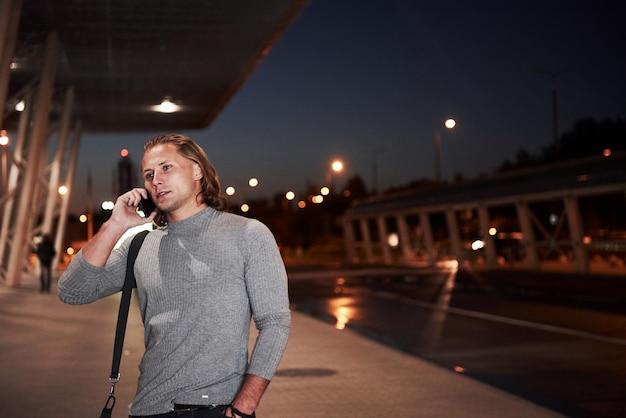 道路の近くの夜の街を歩いて電話で会話をしているスタイリッシュな若い男