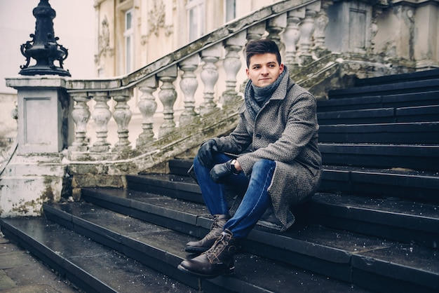 Young stylish man in warm gray coat and leather gloves sitting on the stairs.