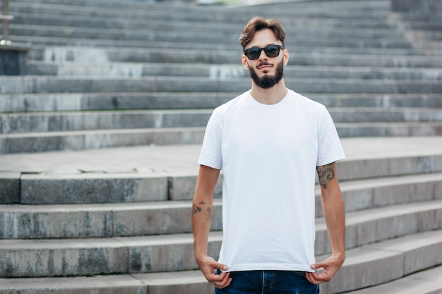 A young stylish man with a beard in a white t-shirt and glasses
