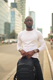 Молодой стильный мужчина в очках держит рюкзак на улице под солнечным светом