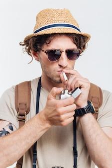 Молодой стильный человек с ретро камерой для некурящих сигарет, изолированные на белом фоне
