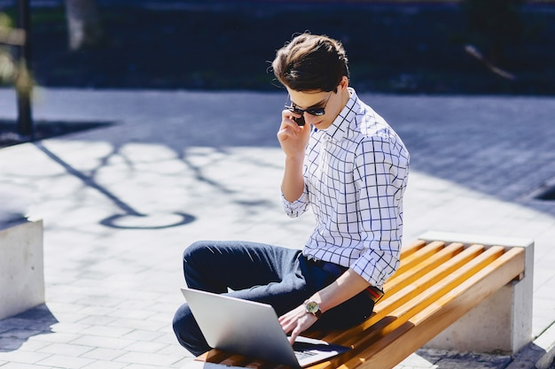 Young stylish man work on laptop at park on sunny day