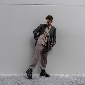 Young stylish model guy in fashionable clothes with shirt, jacket, trousers and shoes posing near gray wall