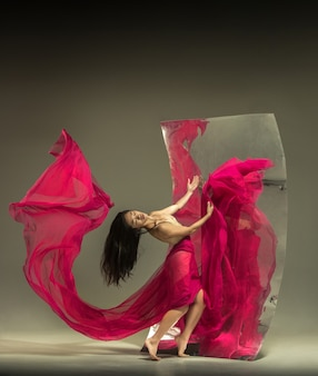 Giovane ed elegante ballerina moderna su marrone con specchio