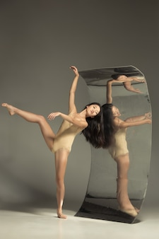 Young and stylish modern ballet dancer on brown with mirror