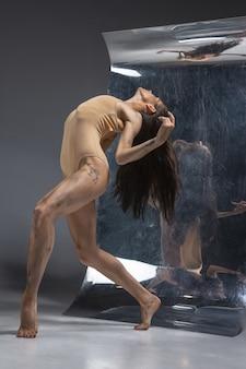 Giovane ed elegante ballerina moderna sulla parete grigia con i riflessi di specchio e illusione sulla superficie