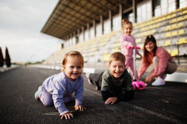 屋外で4人の子供を持つ若いスタイリッシュな母親。スポーツの家族は、スクーターやスケートで屋外で自由な時間を過ごします。アスファルトにチョークで塗った。