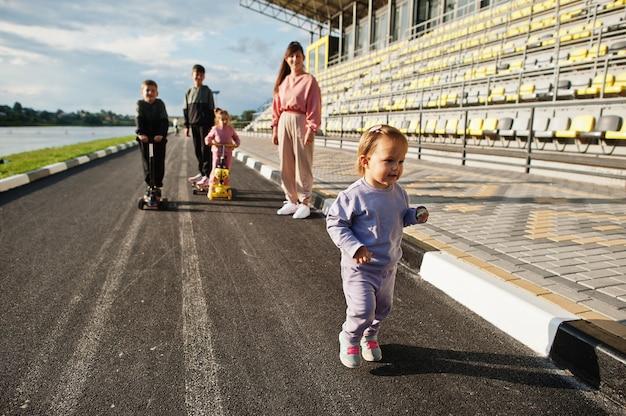屋外で4人の子供を持つ若いスタイリッシュな母親。スポーツの家族は、スクーターやスケートで屋外で自由な時間を過ごします。