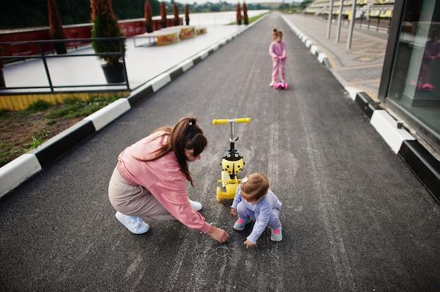 屋外で2人の女の子と若いスタイリッシュな母親。スポーツ家族はスクーターで屋外で自由な時間を過ごします。アスファルトにチョークで塗った。