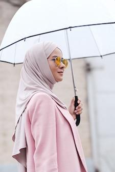 Молодая стильная мусульманская женщина в хиджабе, солнцезащитных очках и розовом кардигане держит зонтик, стоя под дождем в городской среде