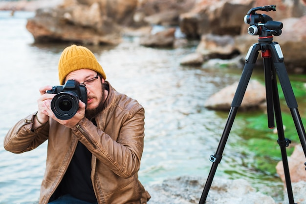 Young stylish photographer sitting on rock and making photo of you