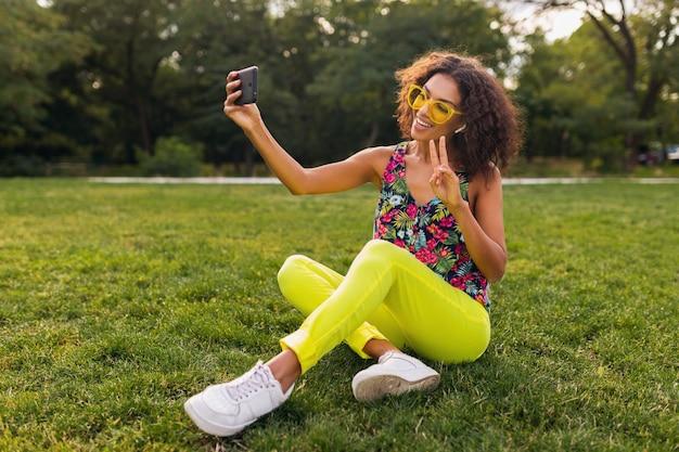 Молодая стильная позитивная темнокожая женщина, делающая селфи-фото, слушая музыку на беспроводных наушниках, развлекается в парке, летняя мода, красочный хипстерский наряд