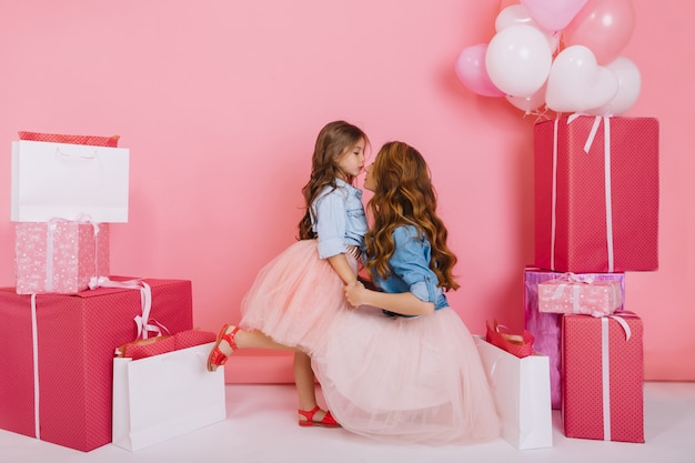 Young stylish pretty woman congratulates daughter in lush skirt on birthday holding her by the hands on pink background. little girl standing on one leg thanks her cute  mother for gifts on holiday