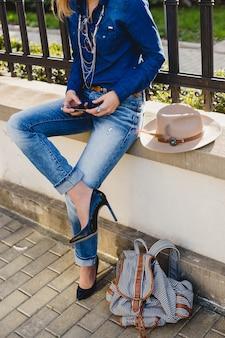 Молодая стильная красивая женщина, держащая телефон, одетая в джинсовую рубашку и джинсы