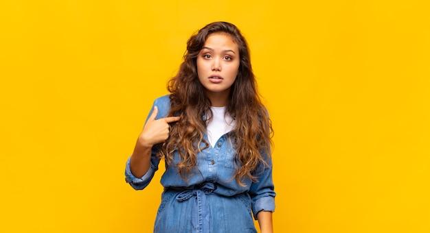 黄色の背景に若いスタイリッシュなきれいな女性