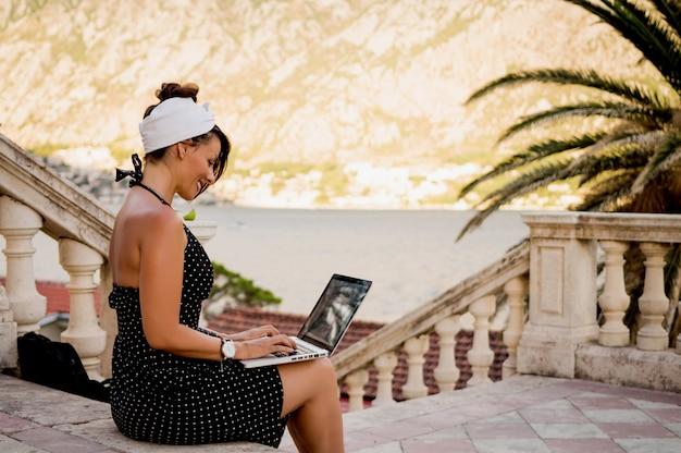 Young stylish pretty woman using laptop outside.