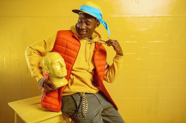 黄色のトーンでスタジオで若いスタイリッシュなラッパーのポーズ
