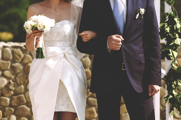 Young stylish and rich bride and groom hold hands on a wedding ceremony on a background of green arch