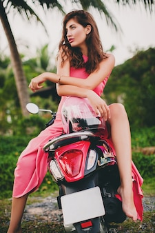 Young stylish sexy beautiful woman in pink dress on scooter motorbike