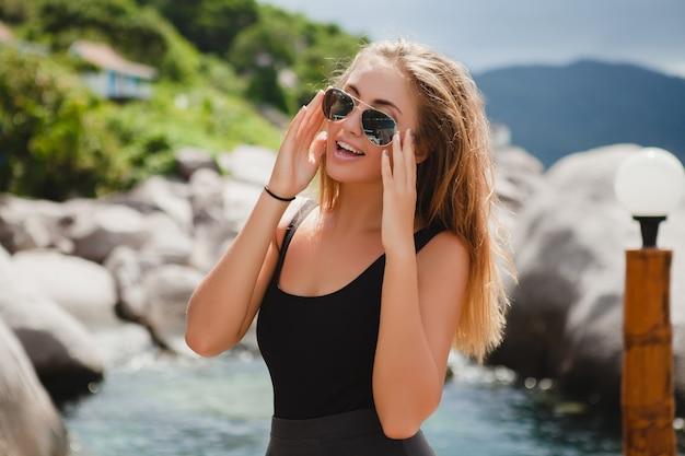 Giovane donna alla moda sexy hipster in vacanza, occhiali da sole aviator, felice, sorridente, godersi il sole, paesaggio laguna blu isola tropicale