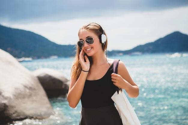休暇中に買い物袋、飛行士のサングラス、ヘッドフォン、音楽を聴いて、幸せな、太陽を楽しんで、熱帯の島の青いラグーンの風景を持つ若いスタイリッシュなセクシーな流行に敏感な女性