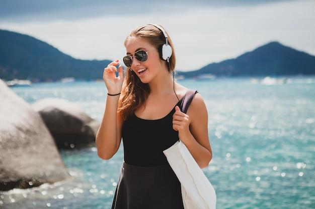 Молодая стильная сексуальная хипстерская женщина с сумкой для покупок во время отпуска, солнцезащитные очки-авиаторы, наушники, слушает музыку, счастлива, наслаждается солнцем, тропическим островом, пейзаж голубой лагуны