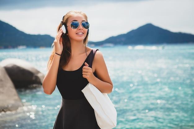 Giovane donna alla moda sexy hipster con una borsa della spesa durante le vacanze, occhiali da sole aviator, cuffie, ascoltare musica, felice, godersi il sole, paesaggio laguna blu isola tropicale