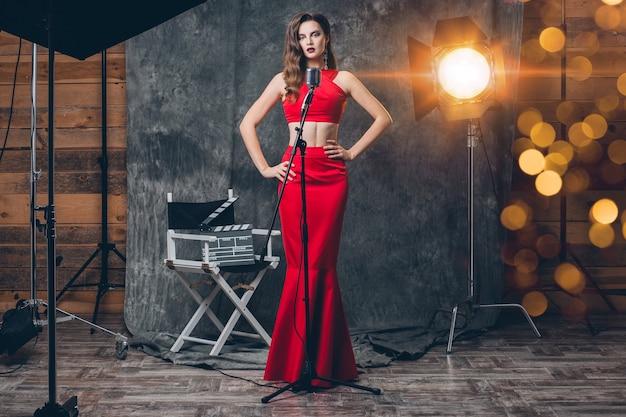 Giovane donna sexy alla moda sul cinema dietro le quinte, celebrando, abito da sera in raso rosso