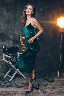 Young stylish sexy woman on cinema backstage, celebrating with a glass of champagne