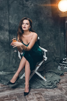 Giovane donna sexy alla moda sul cinema dietro le quinte, festeggia con un bicchiere di champagne