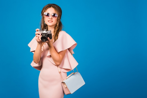 ピンクの高級ドレス、夏のファッションのトレンド、シックなスタイル、サングラス、スタイリッシュなセクシーな女性、ビンテージカメラで写真を撮る
