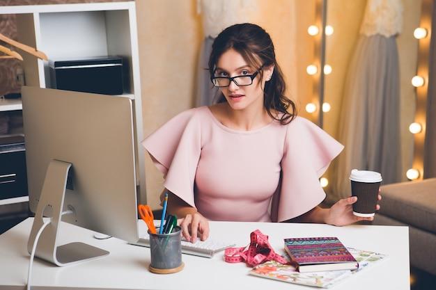 Молодая стильная сексуальная женщина в розовом роскошном платье, летняя тенденция, шикарный стиль, модельер, работающий в офисе на компьютере