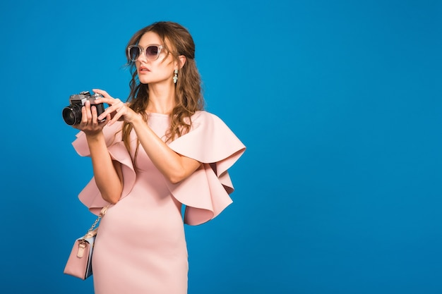 Young stylish sexy woman in pink luxury dress, summer fashion trend, chic style, sunglasses, blue studio background, taking pictures on vintage camera
