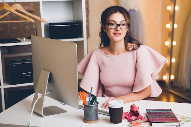Giovane donna sexy alla moda in abito di lusso rosa, tendenza estiva, stile chic, stilista che lavora in ufficio sul computer