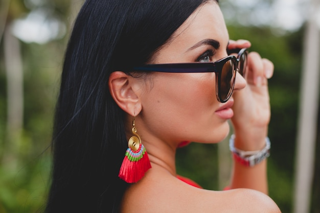 Young stylish sexy woman in red summer dress standing on terrace in tropical hotel, palm trees background, long black hair, sunglasses, ethnic earrings, sunglasses, looking forward, close up