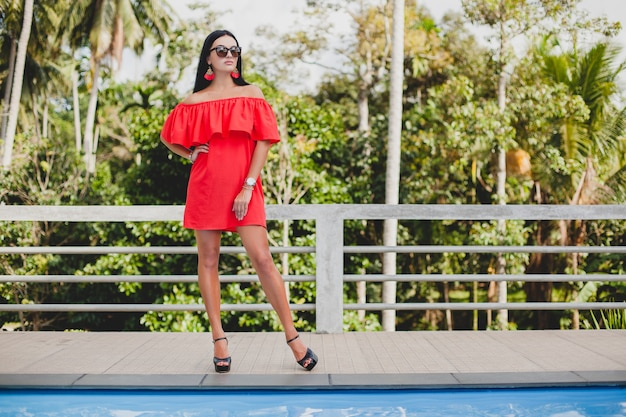 Giovane donna sexy elegante in abito estivo rosso in piedi sulla terrazza in hotel tropicale, sfondo di palme, lunghi capelli neri, occhiali da sole, orecchini etnici, occhiali da sole, guardando avanti, scarpe tacco alto