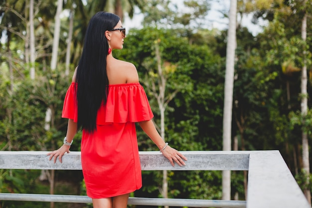 Young stylish sexy woman in red summer dress standing on terrace in tropical hotel, palm trees background, long black hair, sunglasses, ethnic earrings, sunglasses, looking forward