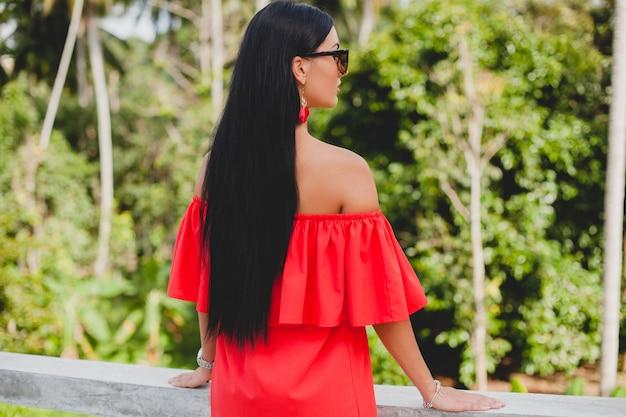 Giovane donna sexy elegante in abito estivo rosso in piedi sulla terrazza in hotel tropicale, sfondo di palme, capelli neri lunghi, occhiali da sole, orecchini etnici, occhiali da sole, guardando avanti
