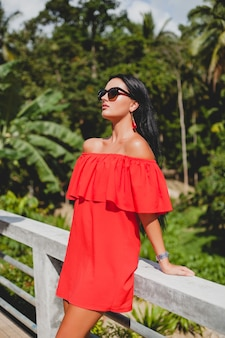 Giovane donna sexy elegante in abito estivo rosso in piedi sulla terrazza in hotel tropicale, sfondo di palme, capelli neri lunghi, occhiali da sole, orecchini etnici, occhiali da sole, sorridente