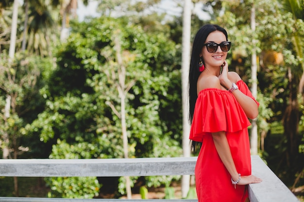 Young stylish sexy woman in red summer dress standing on terrace in tropical hotel, palm trees background, long black hair, sunglasses, ethnic earrings, sunglasses, smiling