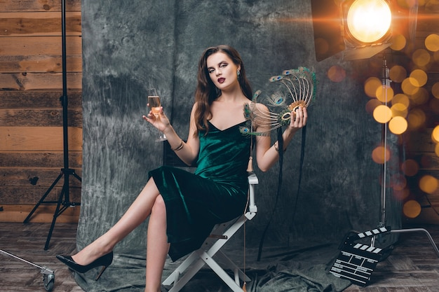 Young stylish sexy woman sitting in chair on cinema backstage, celebrating with a glass of champagne