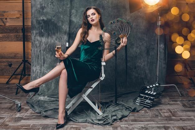 Giovane donna sexy alla moda che si siede sulla sedia sul dietro le quinte del cinema, festeggia con un bicchiere di champagne