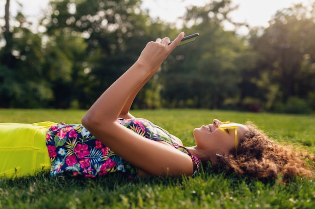 Giovane donna di colore sorridente elegante che utilizza smartphone che ascolta la musica sugli auricolari senza fili divertendosi nel parco, stile variopinto di modo di estate, sdraiato sull'erba, occhiali da sole gialli