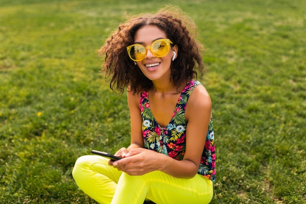 Young stylish smiling black woman using smartphone listening to music on wireless earphones having fun in park