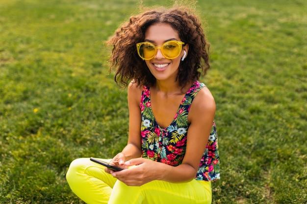 Giovane donna di colore sorridente elegante che utilizza smartphone che ascolta la musica sugli auricolari senza fili divertendosi nel parco