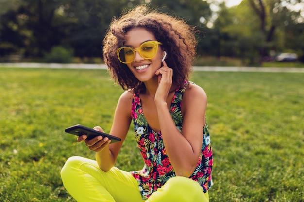 公園で楽しんでいるワイヤレスイヤホンで音楽を聴いているスマートフォンを使用して、若いスタイリッシュな笑顔の黒人女性、夏のファッションカラフルなスタイル、草の上に座って、黄色のサングラス