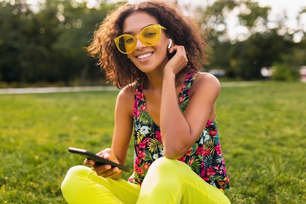 Молодая стильная улыбающаяся темнокожая женщина, использующая смартфон, слушая музыку на беспроводных наушниках, веселится в парке